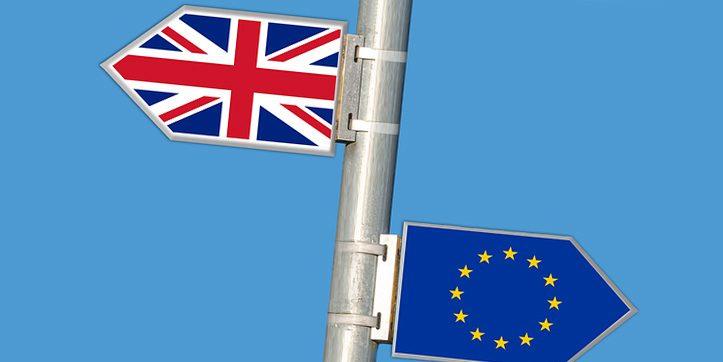 Указатели ЕС и Великобритания на голубом фоне на железном шесте
