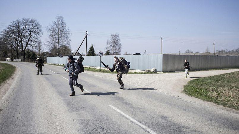 Молодые добровольцы бегут по дороге в литовскую деревню / Фото: theatlantic.com