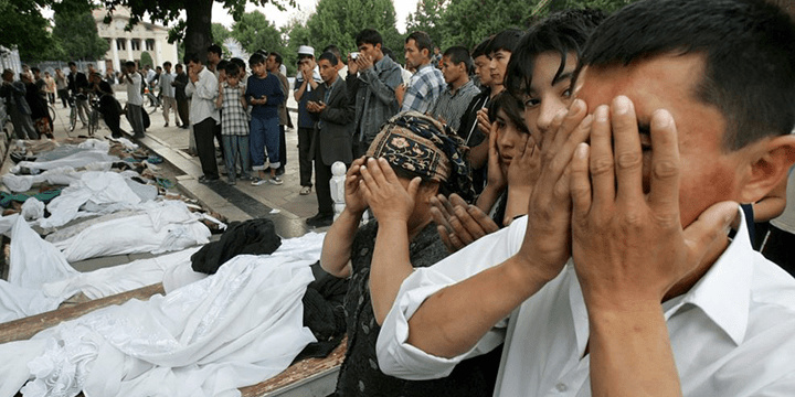 Люди молятся около тел жертв расстрела в Андижане. 14 мая 2005 года